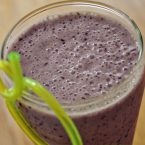 berry smoothie in a glass with a curly green straw