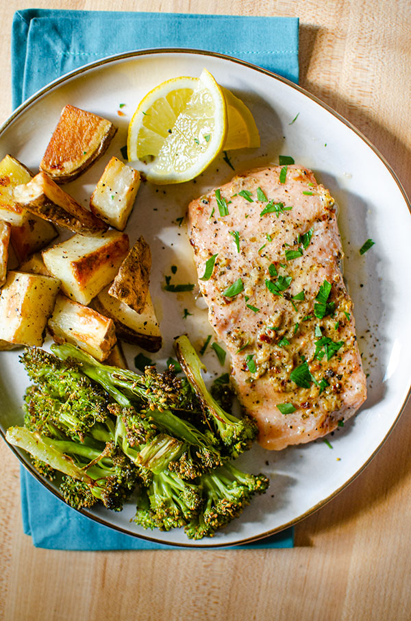 Baked trout fillet on a plate with roasted potatoes, broccoli and lemon wedges.