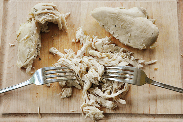 This recipe for all-purpose poached chicken breasts is made with garlic, onion and oregano for a simple low-fat shredded chicken recipe. | livinglou.com