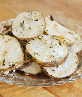 Sliced herb grilled potatoes on a plate