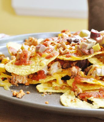 A plate of loaded nachos with cheese, olives, ground turkey and chips.