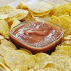 homemade salsa in a bowl surrounded by yellow corn chips