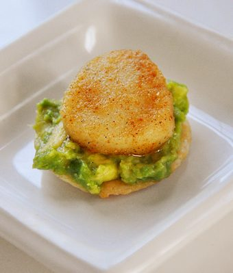 spicy seared scallops on top of avocado on a rice cracker