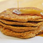 A stack of whole wheat pumpkin pancakes with a drizzle of maple syrup