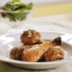 Thyme chicken drumsticks on a plate with a spinach salad in the background