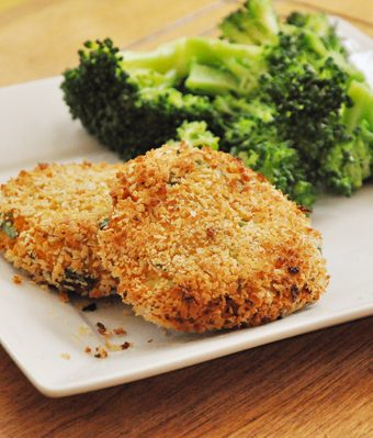 Two salmon cakes on a plate with broccoli