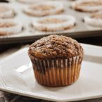 A cinnamon swirl muffin on a plate with a newspaper