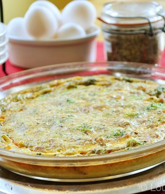 Crustless spinach quiche on a plate with eggs and herbs in the background