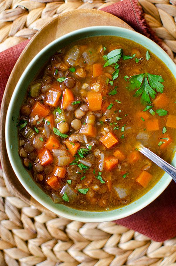 Mediterranean lentil soup in a green bowl on a burgundy napkin.