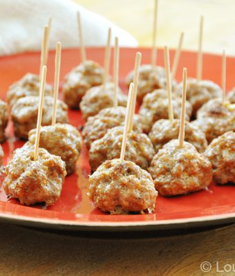 A plate with appetizer meatballs on it with toothpicks in them