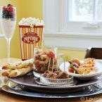 An oscar party spread on a table with seafood salad, appetizer meatballs, popcorn, olive and cheese breadsticks and raspberry fouls