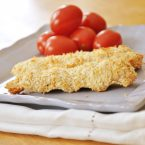 Coconut crusted chicken strips on a plate with cherry tomatoes