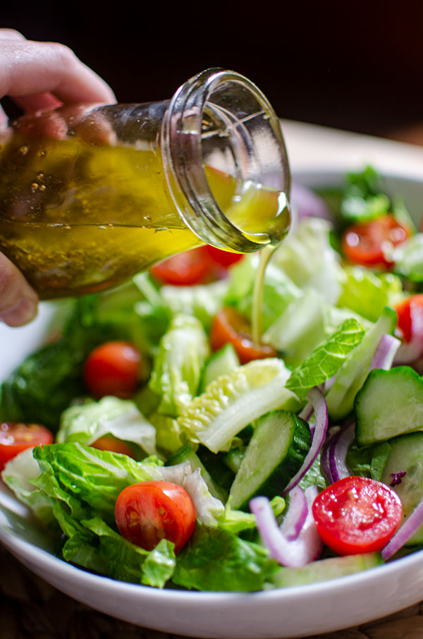 Closeup of vinaigrette being poured on the salad.