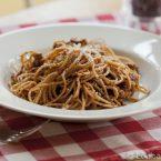A bowl of basil garlic spaghetti sauce on a red checkered napkin
