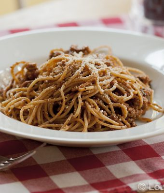 A bowl of basil garlic spaghetti sauce on a red checkered napkin