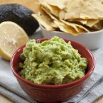 A bowl of easy, fresh guacamole with a plate of chips