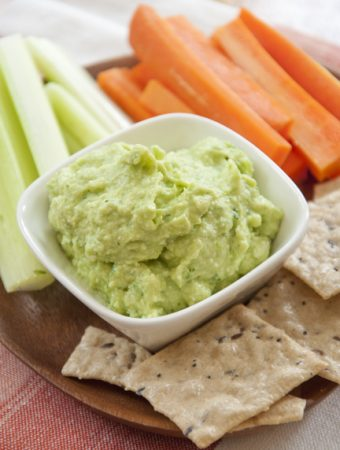 Avocado Feta Dip in a bowl with crackers, carrot slices and celery slices