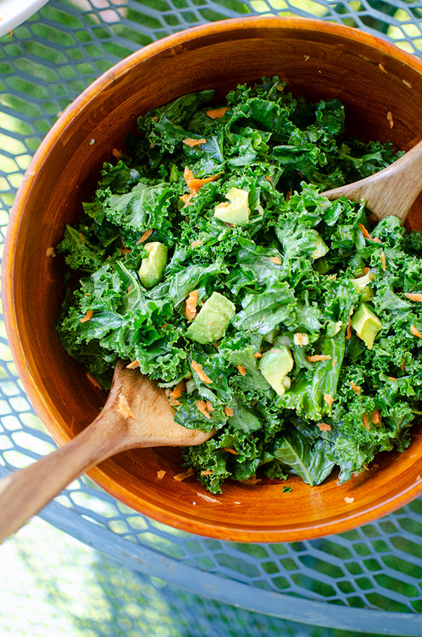 Kale avocado salad in a wooden bowl on an outdoor table.