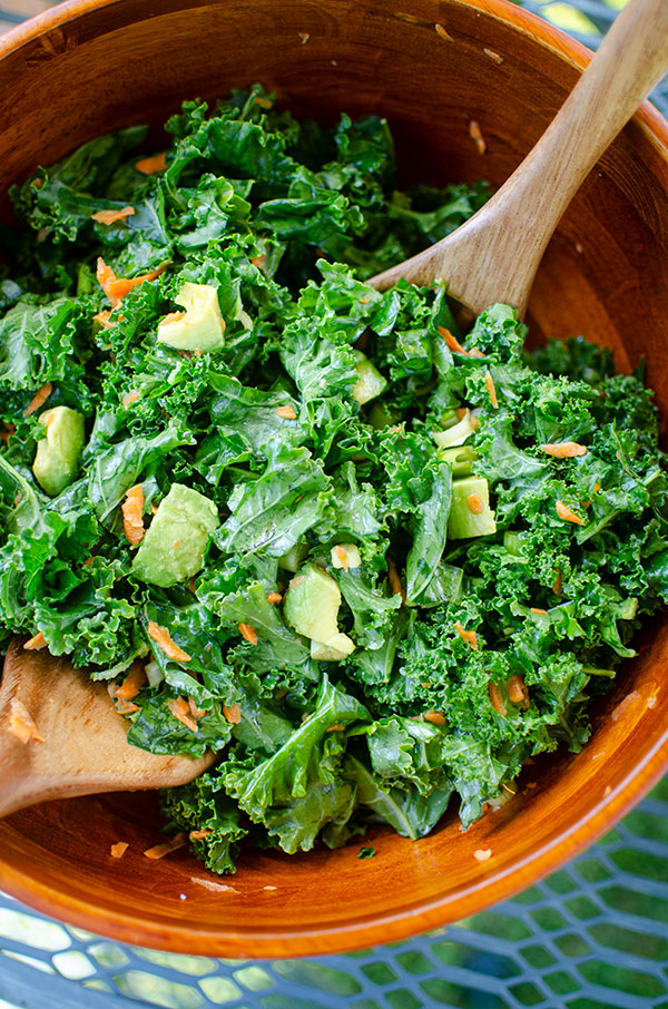 Kale avocado salad in a wooden bowl.