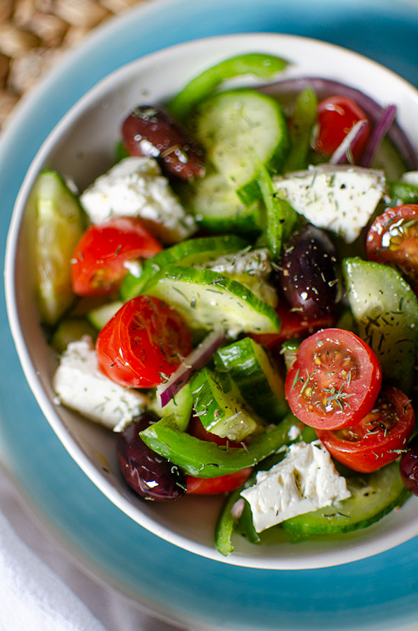 Greek salad in a white bowl with dried thyme sprinkled on top.