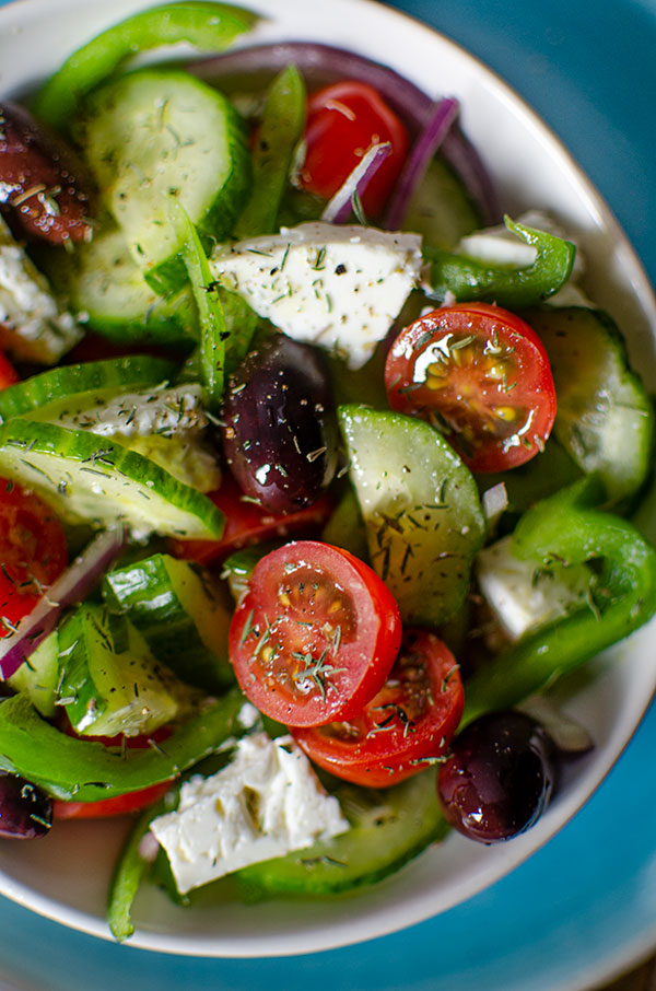 Close up of Greek salad in a white bowl with dried thyme sprinkled on top.