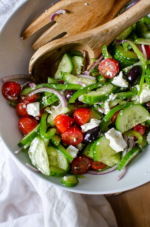 Greek salad in a large white bowl with wooden salad spoons and a white napkin