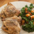 closeup of perfectly roasted chicken thighs on a plate with sauteed kale and sweet potatoes