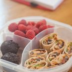 vegetarian-taco-wraps in a lunchbox with raspberries and chocolate muffins