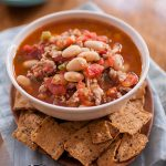 Turkey and white bean chili in a white bowl with crackers