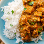 A plate with rice and slow cooker butter chicken with cilantro sprinkled on top