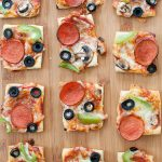 puff pastry pizza bites cut into squares on a cutting board