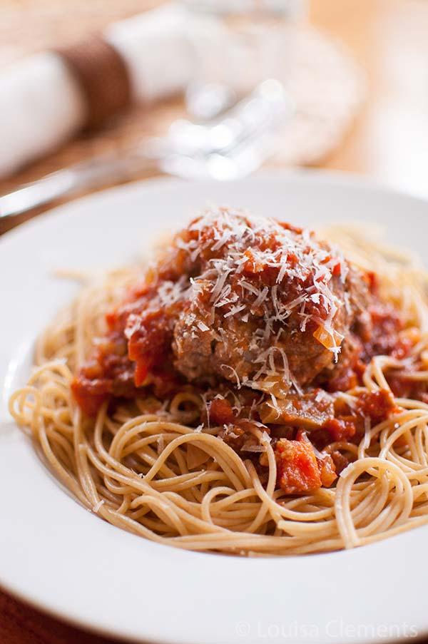 Slow cooker meatballs in tomato sauce serve on pasta