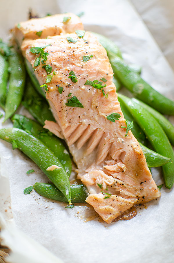 Cooked salmon fillet with a piece taken out of it served on top of sugar snap peas.