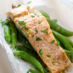 Cooked salmon on top of sugar snap peas in a parchment paper package.