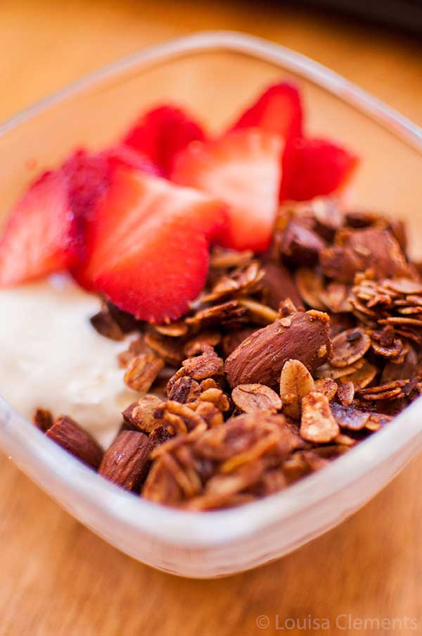 homemade honey almond granola with yogurt and strawberries in a bowl.