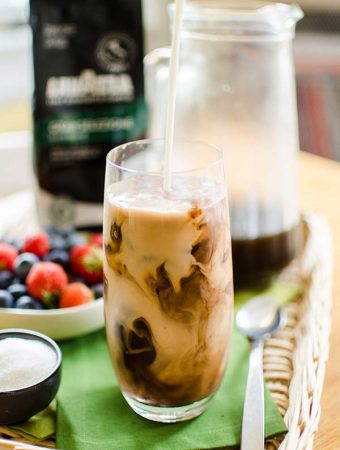 Milk being poured into iced coffee with mocha ice cubes