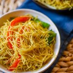 Vegetarian singapore noodles in a white bowl on a blue napkin