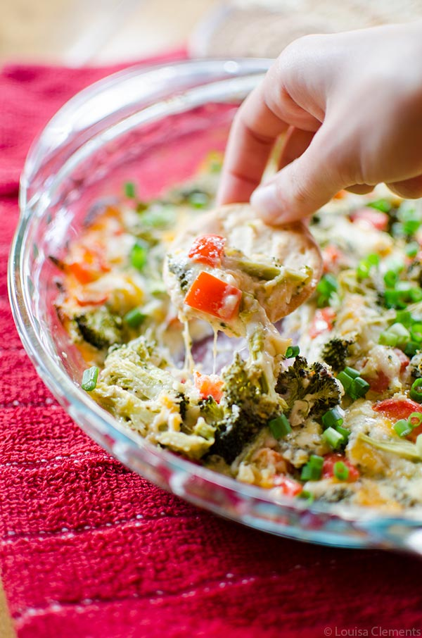 The perfect appetizer for entertaining or for game day, this cheesy broccoli dip is a healthier vegetarian option loaded with broccoli and red peppers.   livinglou.com