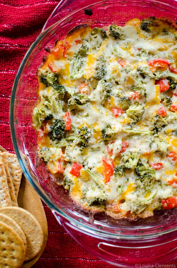 The perfect appetizer for entertaining or for game day, this cheesy broccoli dip is a healthier vegetarian option loaded with broccoli and red peppers. | livinglou.com
