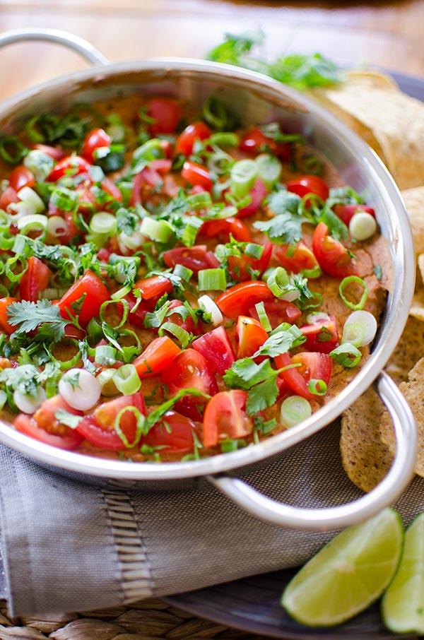 A cheesy refried bean dip with tomato, green onion and cilantro.   livinglou.com