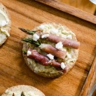 Prosciutto wrapped asparagus with pesto goat cheese on crackers is the perfect holiday appetizer for a cocktail party. | Livinglou.com