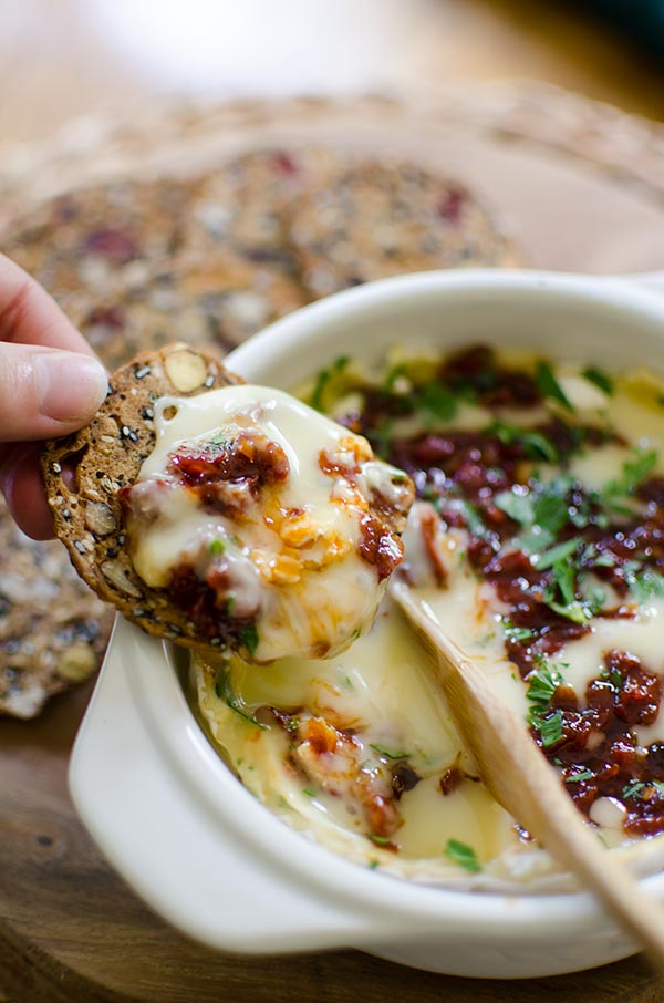 Baked Camembert cheese with sun dried tomatoes and red pepper jelly is the perfect appetizer. | livinglou.com