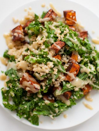 Sweet potato, kale and quinoa come together with a creamy tahini dressing on a plate
