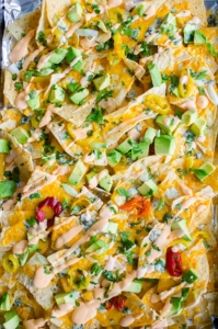 Enjoy all the flavours of Buffalo chicken in this nacho recipe for spicy Buffalo nachos with tons of cheddar and blue cheese, hot peppers and a Buffalo sour cream. | livinglou.com