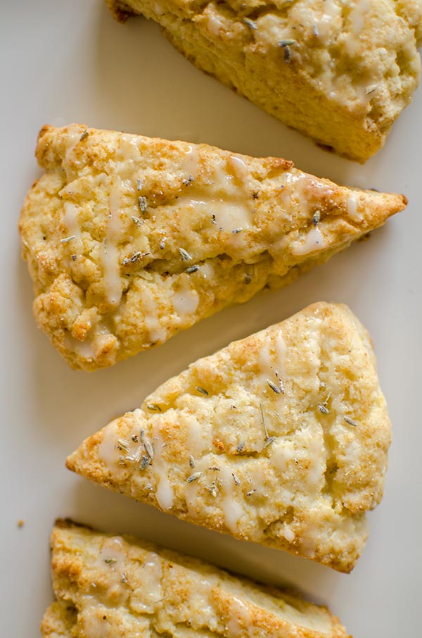 Light and fluffy homemade lemon scones with a lemon glaze and sprinkled with lavender. | livinglou.com