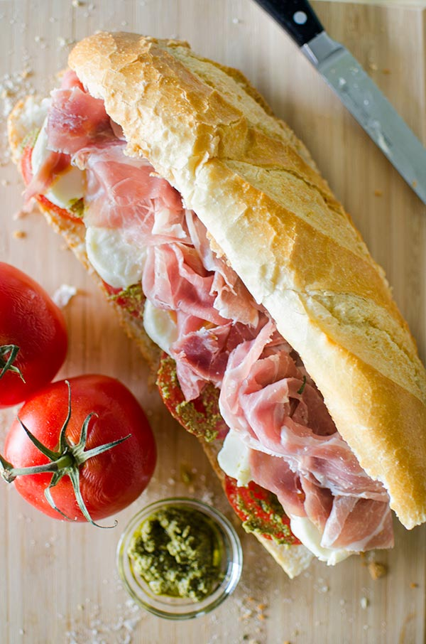 Prosciutto mozzarella and pesto marinated tomato sandwich. | livinglou.com
