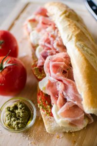 Prosciutto mozzarella and pesto marinated tomato sandwich. | livinglou.com