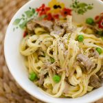 Braised lamb ragu with peas tossed with pasta in a bowl.