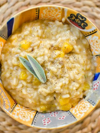 Butternut squash risotto in a colourful bowl with a fresh sage garnish.