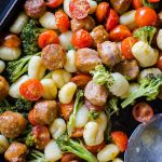 Closeup on sheet pan oven baked gnocchi with sausage and vegetables on a baking sheet with a spoon.